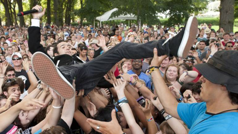 Pete Wentz of Black Cards frolics with festival-goers at BMI's Lollapalooza stage, August 5 in Chicago.