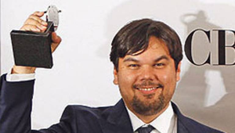Robert Lopez shows off one of his trophies for <em>The Book of Mormon</em> at the 2011 Tony Awards.