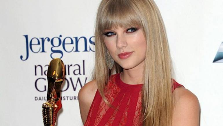Pictured: Taylor Swift shows off her new Woman of the Year trophy at the 2012 Billboard Music Awards.
