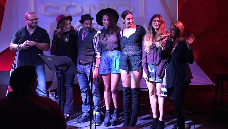 BMI's Joey Mercado, Karen Inderbitzin, Elsten Torres, Raquel Sofia, Manu Manzo, Camila Luna and BMI's Delia Orjuela pose for a photo on stage during BMI's Acoustic Lounge, held in Miami on October 14.