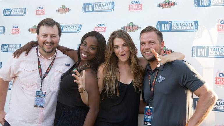 BMI's Mason Hunter and BMI singer-songwriters Jessy Wilson and Kallie North of Muddy Magnolias pose with sponsor Texas Roadhouse's Tyler Durham before the duo's performance at the BMI Tailgate stage at CMA Fest.
