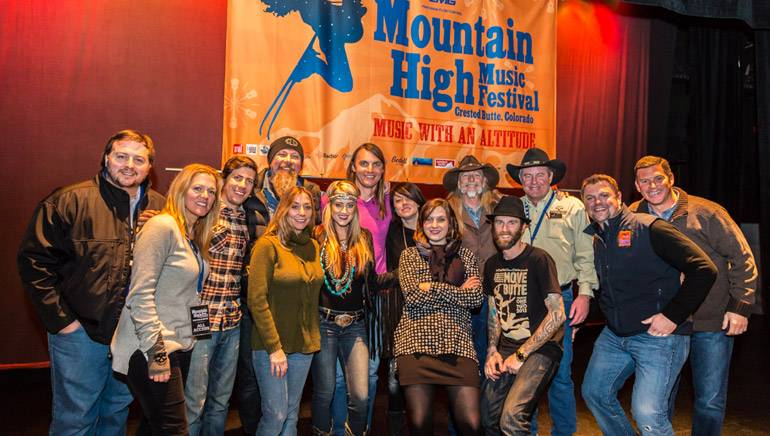 BMI executives and songwriters pose in front of the banner for the inaugural Mountain High Music Festival. BMI songwriter and 2013 Country Icon Dean Dillon was the host of the event.