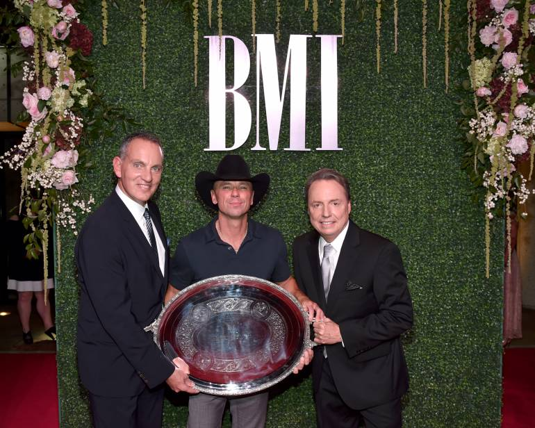 BMI President & CEO Mike O'Neill and BMI Vice President, Writer/Publisher Relations Jody Williams pose with 2016 President's Award recipient Kenny Chesney.