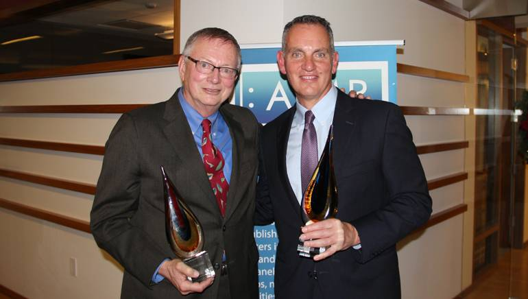 peermusic's Ralph Peer II and BMI President and CEO Mike O'Neill with their awards at AIMP's holiday event.