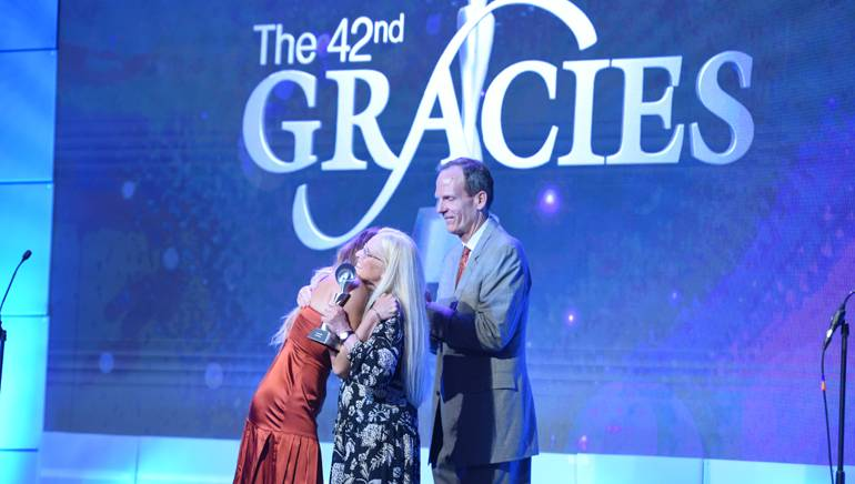 BMI's Barbara Cane and Dan Spears present the very first Gracies Impact Award to Rachel Platten.