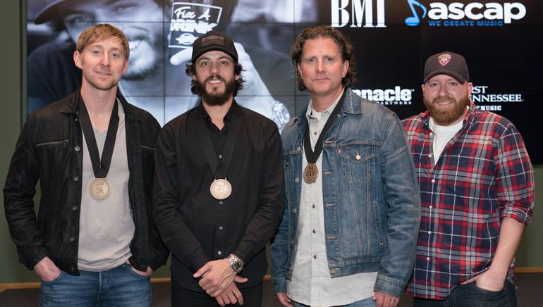 "Ashley Gorley, Chris Janson, Chris DuBois and producer Brent Anderson gather while celebrating their No. 1 song ""Fix A Drink."""