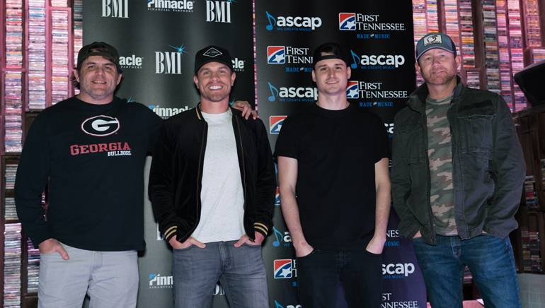 """""""Small Town Boy"""" songwriters Rhett Akins, Kyle Fishman and Ben Hayslip gather with Dustin Lynch while celebrating their No. 1 song."""