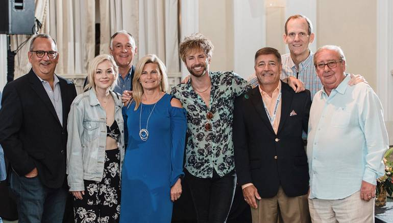 Gathered (L-R) for a photo before the performance at the Florida Association of Broadcasters annual conference are: Univision Station Group Senior Vice President and Regional Director and FAB outgoing Board Chair Luis Fernandez-Rocha, BMI songwriter Emily Kinney, Holladay Broadcasting President/Owner and the 2018 FAB Bill Brooks Award-winner Bob Holladay, Holladay Broadcasting Vice President of Sales Sherri Holladay, BMI songwriter Paul McDonald, Sinclair Broadcast Group Market Manager-West Palm Beach and FAB Board Chair Mike Pumo, BMI's Dan Spears and FAB Pres/CEO Pat Roberts.