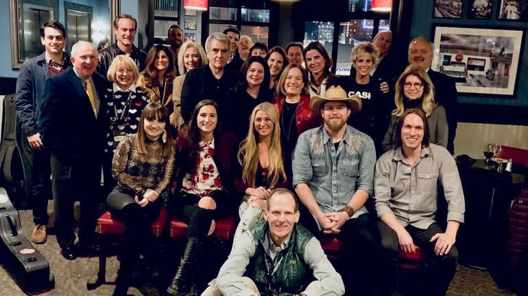 Pictured (L-R) with BMI licensing customers and association partners after the annual CRS BMI songwriter dinner are: (seated) BMI songwriters, Rachele Lynae, Angie K., Julia Cole, Lance Carpenter and Jimmy Nash (front): BMI's Dan Spears.