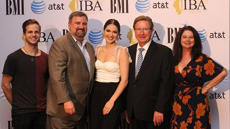 Gathered (L-R) after the performance at the IBA's Silver Dome awards dinner are: guitarist Kevin Monaghan, IBA Chairman of the Board and President of ABC 7 Chicago John Idler, BMI singer-songwriter Hannah Ellis, IBA President and CEO Dennis Lyle and BMI's Jessica Frost.