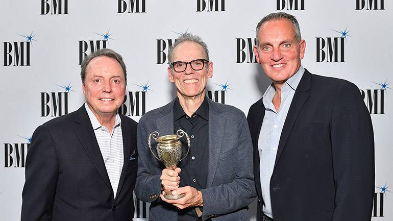 BMI's Jody Williams, 2019 BMI Troubadour John Hiatt and BMI's Mike O'Neill pose with the vintage Troubadour trophy.