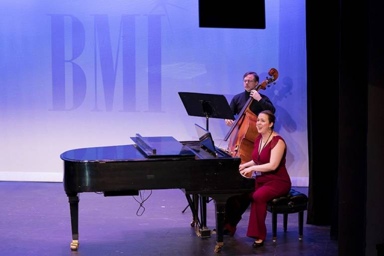"Composer and lyricist Erin Murray Quinlan performs the quirky medley ""What I Mean"" from ""God Save Queen Pam"" at the 2019 BMI Lehman Engel Workshop Showcase. Pictured on bass is Mark Wade."