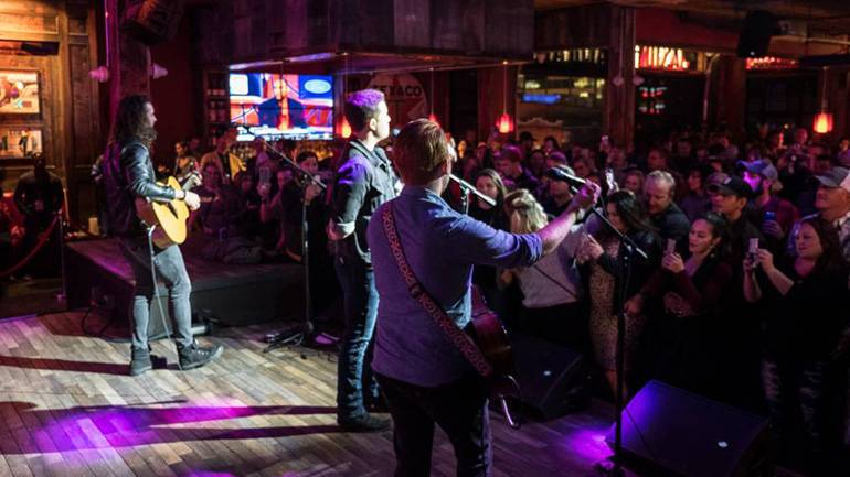 "Scotty McCreery address the special audience of veterans and their families and friends at the ""iHeartCountry: One Night for Our Military"" BMI Guitar Pull at Jason Aldean's Kitchen in Nashville."
