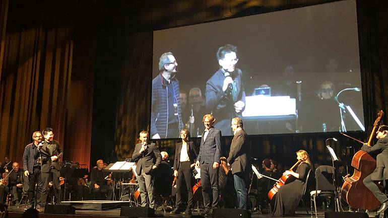 """Composers Jesper Kyd and Sarah Schachner are introduced to the crowd by actor Roger Craig Smith, who voices the main character, Ezio, from """"Assassin's Creed."""""""