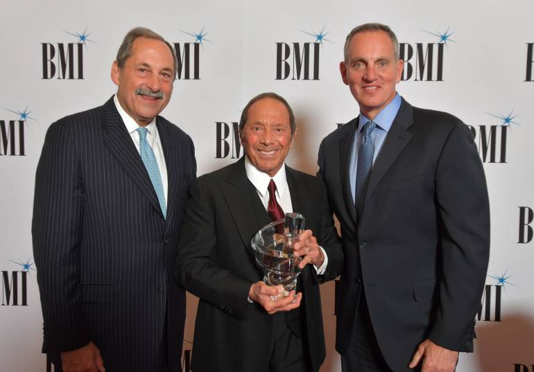 Michael Fiorile, Chairman, BMI Board of Directors & Chairman and CEO, The Dispatch Printing Company and BMI President and CEO Mike O'Neill present Paul Anka with the BMI Board of Directors Award at the 71st Annual BMI/NAB Dinner.