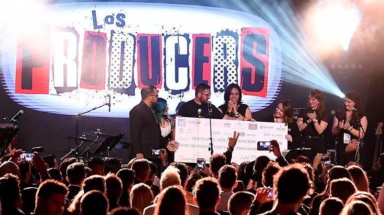 The 2019 Los Producers charity event raised more than $135,000 for the Michael J. Fox Foundation. On stage receiving the check are (L-R) BMI's Joey Mercado and Mary Russe, Rebeleon Entertainment's Sebastian Krys, BMI's Alex Flores and the Foundation representatives.